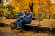 canvas print picture - Young loving couple on a bench in autumn park