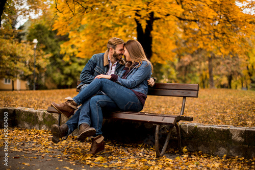 Fototapeta Young loving couple on a bench in autumn park obraz