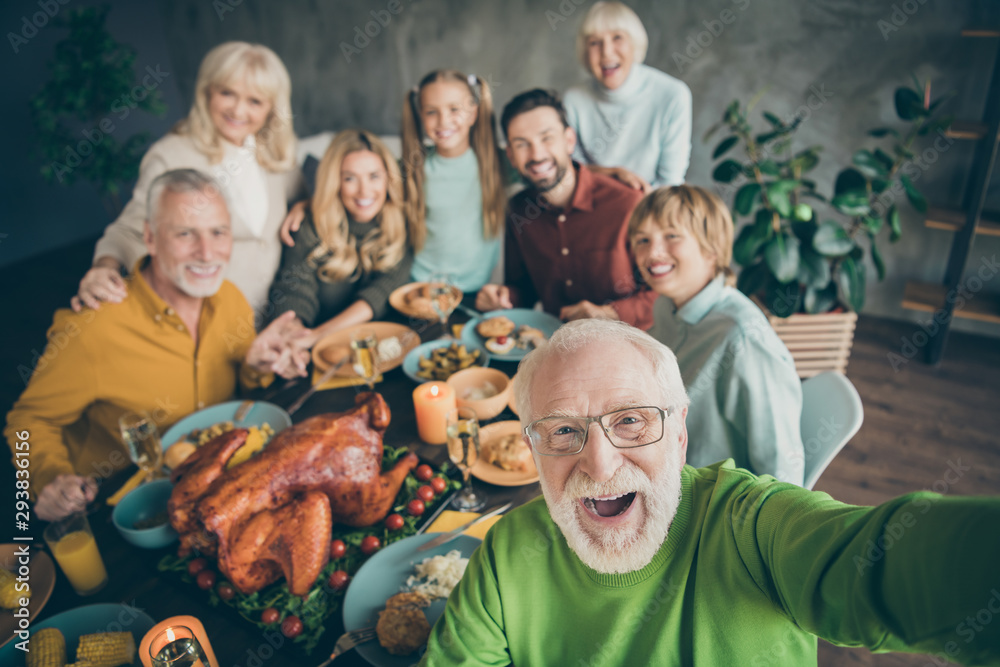 Fototapeta Photo of big family sit hugging feast dishes table around roasted turkey multi-generation relatives grey-haired grandpa making group selfies in living room indoors