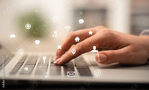 Business woman hand typing on keyboard with application icons around - 293836322