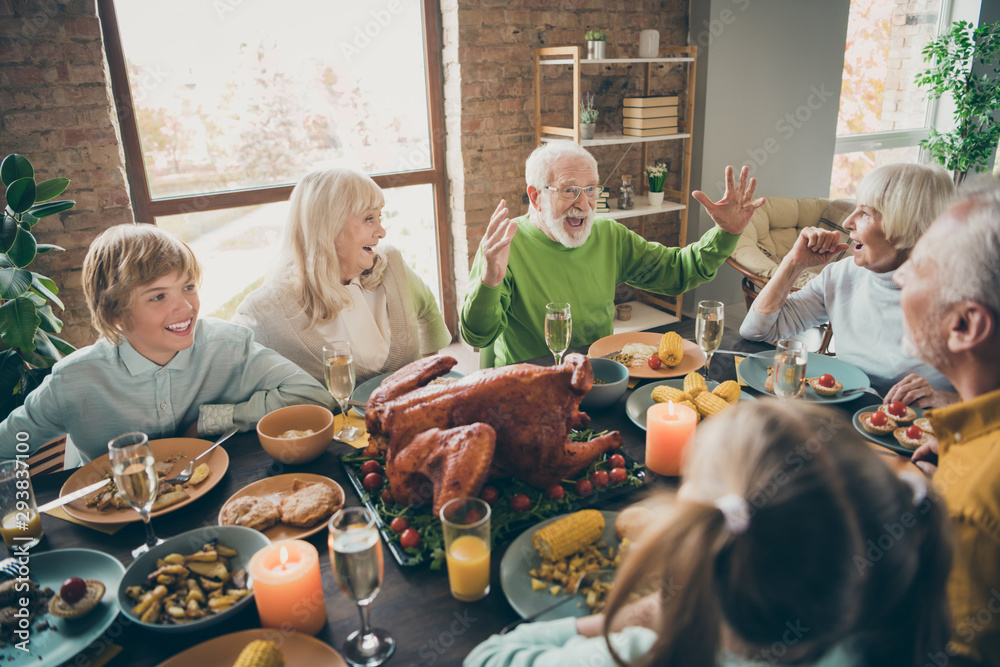 Fototapeta Photo of full family reunion gathering sit feast dishes chicken table communicating fall november autumn holiday multi-generation in evening living room indoors