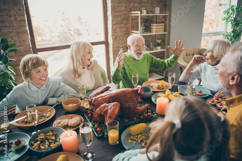 Spoed Foto op Canvas Kruidenierswinkel Photo of full family reunion gathering sit feast dishes chicken table communicating fall november autumn holiday multi-generation in evening living room indoors