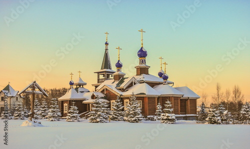 Small log church surrounded by snowy firs - 293837952