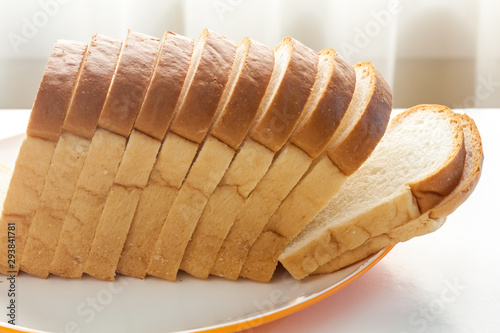 Loaf of bread sliced in a plate on a table near window with sunlight