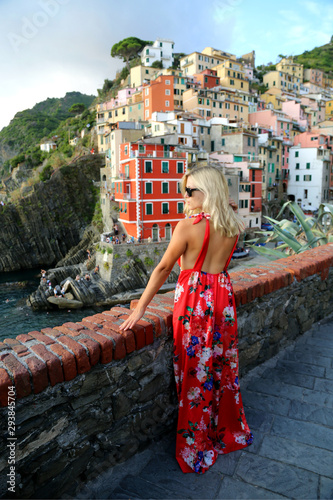 Photographie  Blond girl traveller in a long red dress enjoying the view of Cinque Terra Liguria Italy