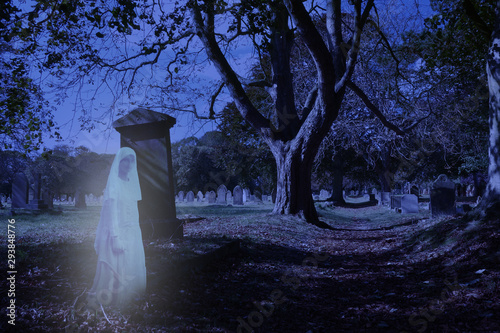 Ghosts appear during Halloween at the Church Cemetery - Transparent blue white Victorian female ghostly figure floating past large grave stone in cemetery late at night with spooky shadows and trees