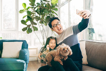 Young Father And Girl Taking Selfie At Home
