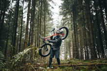 Man Carrying His Mountain Bike On A Forest Trail
