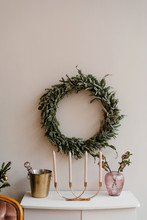 Fir Wreath Hanging On Wall Near Candles And Bucket