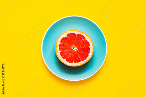 Recess Fitting Food Top view - Bright fresh grapefruit on color plate on yellow background. Concept of vegan diet.