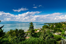 Top View Of The Green Coast And The Port Of Thonon Les Bains, Boats, Lake Geneva, And The Blue Sky With Clouds.