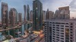 Aerial panoramic view of Dubai Marina residential and office skyscrapers with waterfront night to day transition timelapse before sunrise. Floating boats and yachts