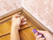 installation and fixing of the baseboard,mounting and assembly plinth,the master screws the skirting board closeup