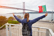 Young woman tourist holding the flag of Portugal in hands and enjoying landscape view on the famous iron bridge 25th of April standing back on the riverside in Lisbon city