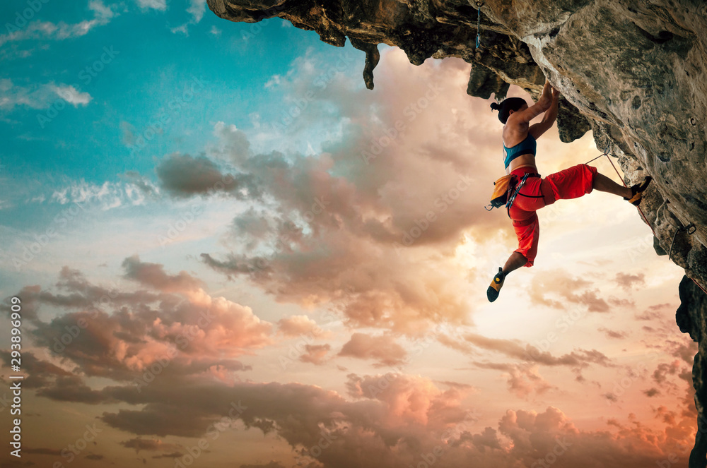Fototapety, obrazy: Athletic Woman climbing on overhanging cliff rock with sunset sky background