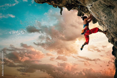 Fotomural Athletic Woman climbing on overhanging cliff rock with sunset sky background