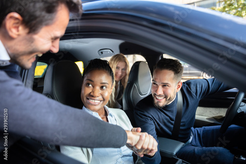 Photo Man Shaking Hanks With Friends Sitting In Car