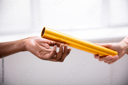 Fotografiet Passing Golden Relay Baton To Other Person