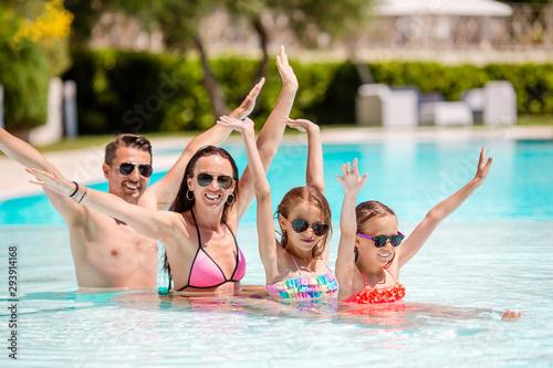 Fotografie, Obraz  Happy family of four in swimming pool