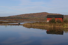 Man Paddling A Canoe From A Red Boat Shed On Eel River, New Brunswick, Canada, In Early Morning On An Autumn Day.