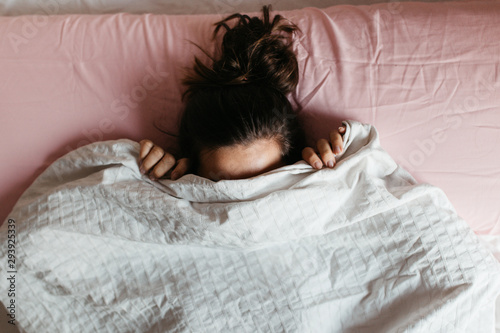 Playful young woman hiding face under blanket while lying in cozy bed on white pillow, pretty curious girl feeling shy peeking from duvet, covering with white sheet, head shot close up Wallpaper Mural