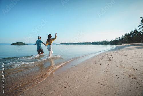 Happy middle aged couple running on a beach