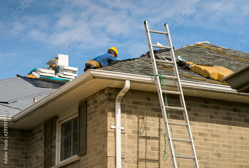 Fotografia Roof worker installing new shingles on a roof of a house
