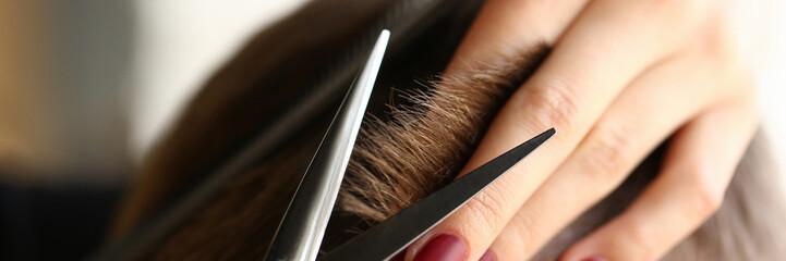 Female hand hold hair scissors aganist hairdresser salon background