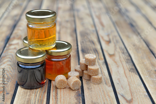 little glass pots of honey and brown sugar on a wooden table