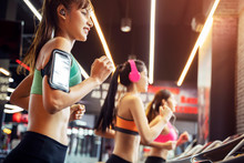Group Of Young Sport Women Running With Happiness Together At Gym. Listening To Music With Wireless Earphone.