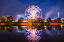 Germany, Illuminated Colorful Big Wheel In Motion And Rollercoaster Of Popular Folk Festival Called Cannstatter Wasen In Stuttgart Bad Canstatt By Night Reflecting In Water