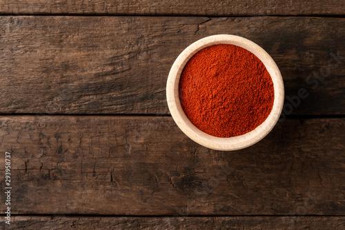 Obraz na plátne Dried red paprika powder in bowl on retro wooden background