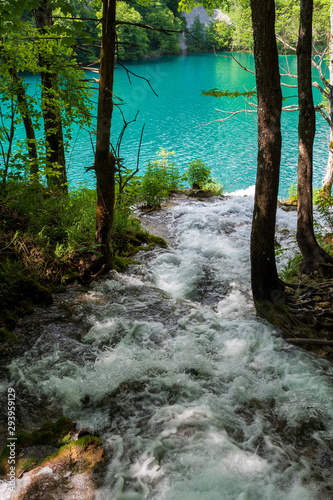 Rushing water cascades down the mountain slope into the crystal clear and azure coloured Lake Milanovac at the Plitvice Lakes National Park, Croatia Wall mural