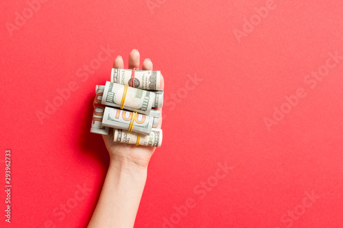 Top view of dollar bills in tubes in female hand on colorful background Tapéta, Fotótapéta