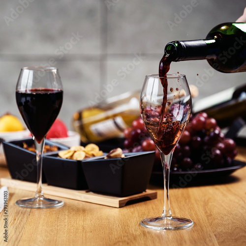 Red wine pouring into a wine glass at a tasting with various types of appetizers.