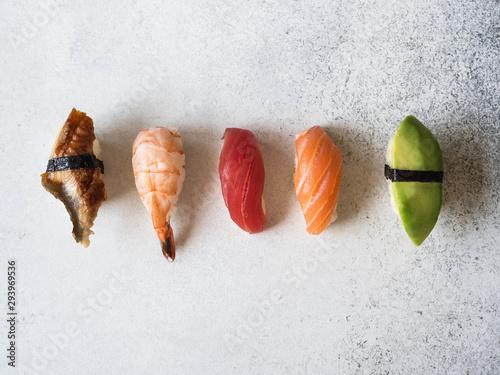 Fotografía  Smoked eel, salmon, tuna, shrimp and avocado sushi on grey background