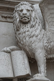 Winged lion with a Bible and a priest at Basilica San Marco in Venice, Italy, summer time, details, closeup