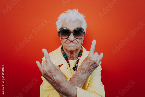 Funny grandmother portraits. Senior old woman dressing elegant for a special event. Rockstar granny on colored backgrounds - 293971145