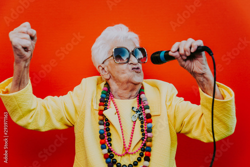 Funny grandmother portraits. Senior old woman dressing elegant for a special event. Rockstar granny on colored backgrounds - 293971163