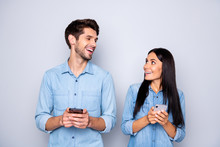 Photo Of Charming Cute Nice Beautiful Couple Of Two People Spouses Holding Their Phones Reacting To Something They Have Seen On Wearing Jeans Denim Isolated Grey Color Background
