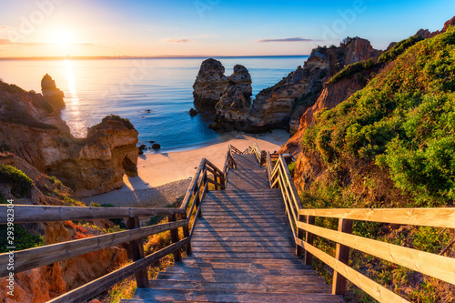 Fototapeta Sunrise at Camilo beach in Lagos, Algarve, Portugal. Wooden footbridge to the beach Praia do Camilo, Portugal. Picturesque view of Praia do Camilo beach in Lagos, Algarve region, Portugal. obraz