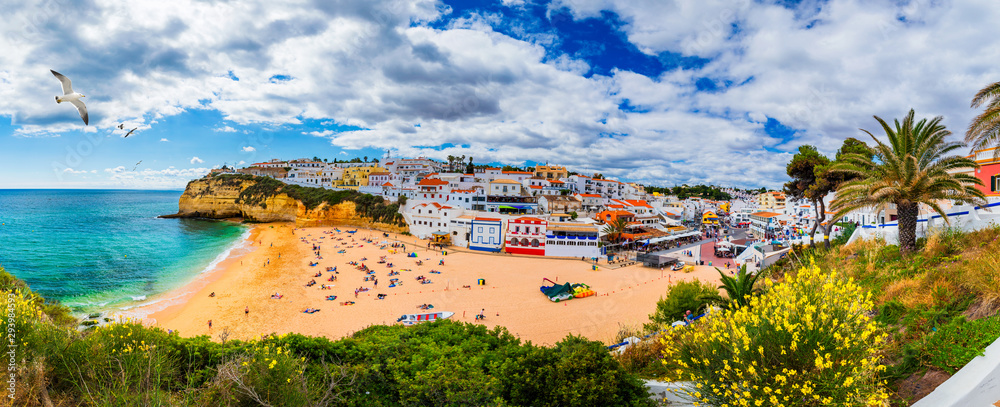 Fototapeta View of Carvoeiro fishing village with beautiful beach, Algarve, Portugal. View of beach in Carvoeiro town with colorful houses on coast of Portugal. The village Carvoeiro in the Algarve Portugal.