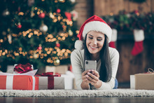 Close Up Photo Of Positive Girl In Santa Claus Hat Lie On Carpet Use Smartphone Send Christmas Congratulation Search Discounts In House With X-mas Comfort Atmosphere Indoors