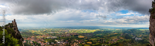 Panoramic view of the Italian countryside and Adriatic Sea (Riviera Romagnola) from Republic of San Marino with the oldest tower (Guaita fortress) on Mount Titan (Monte Titano) on the left