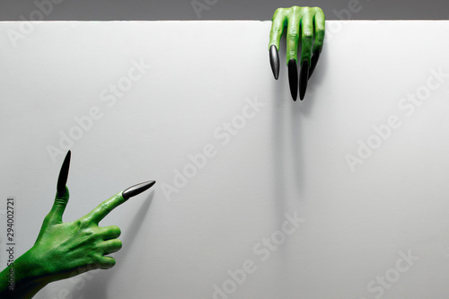 Cadres-photo bureau Fleur Halloween concept. Two green hands hold gray sheet of paper.