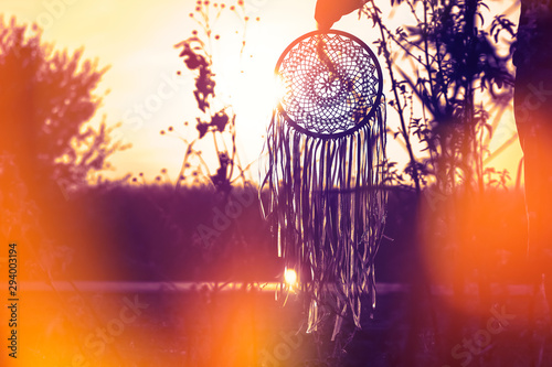 Foto auf Gartenposter Boho-Stil Silhouette of a dream catcher on the background of the road and the sun. Honeymoon trip. Independent travel.