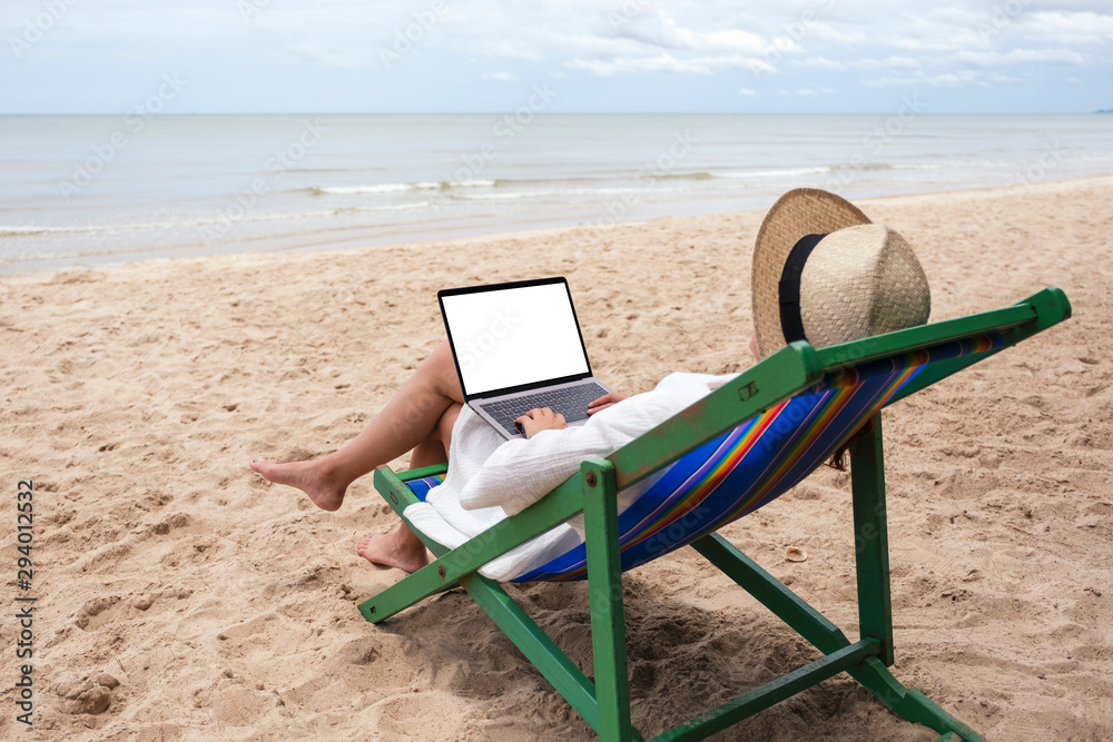 Fototapety, obrazy: Mockup image of a woman using and typing on laptop computer with blank desktop screen while lying down on a beach chair