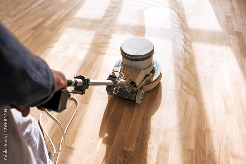 Fototapeta a professional master cleans the floor with a polishing machine obraz