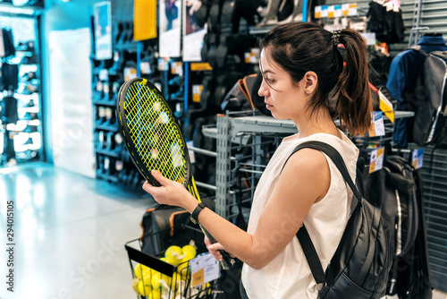 Fotografie, Tablou  girl chooses a tennis racket in a supermarket