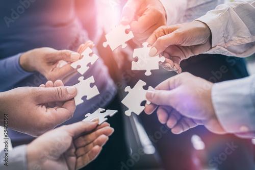 Obraz A group of business people assembling jigsaw puzzle. - fototapety do salonu